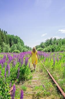 Mulher loira com um vestido amarelo em campo de tremoço. dia ensolarado de verão. relaxamento, férias, conceito de liberdade.