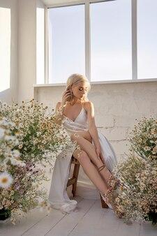 Mulher loira com um vestido de noiva branco sentada perto da janela em frente a um buquê de flores silvestres