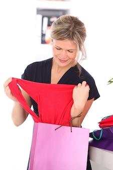 Mulher loira com uma blusa vermelha nas mãos dela
