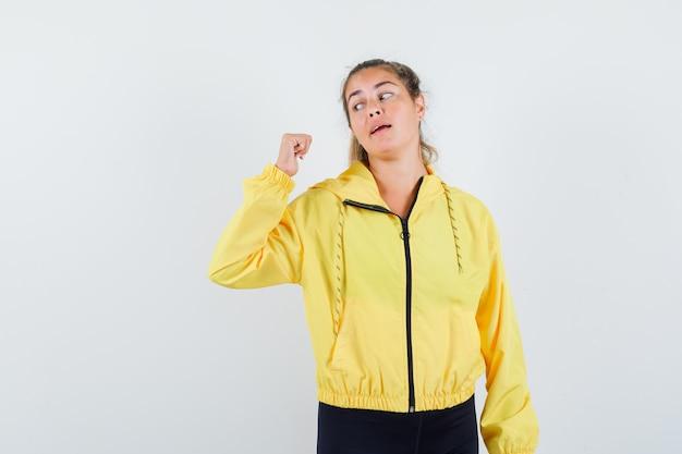 Mulher loira com uma jaqueta militar amarela e calças pretas cerrando os punhos e olhando para ela e olhando com foco