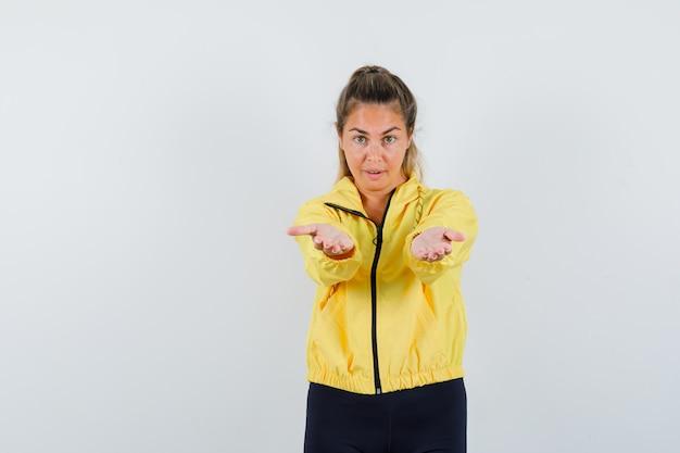 Mulher loira com uma jaqueta militar amarela e calças pretas estendendo as mãos como um convite para vir e parecendo amável