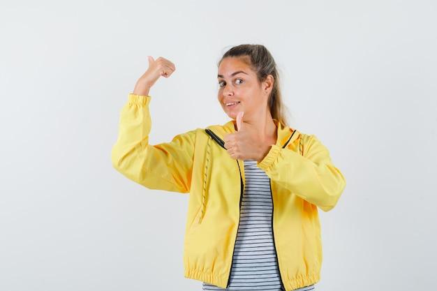 Mulher loira com uma jaqueta militar amarela e camisa listrada apontando para trás com o dedo indicador e mostrando o polegar para cima e parecendo confiante