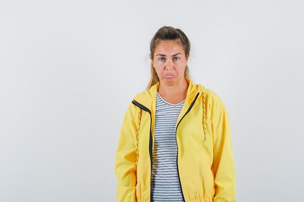 Mulher loira com uma jaqueta militar amarela e camisa listrada em pé, reta, fazendo caretas e posando para a câmera e bonita