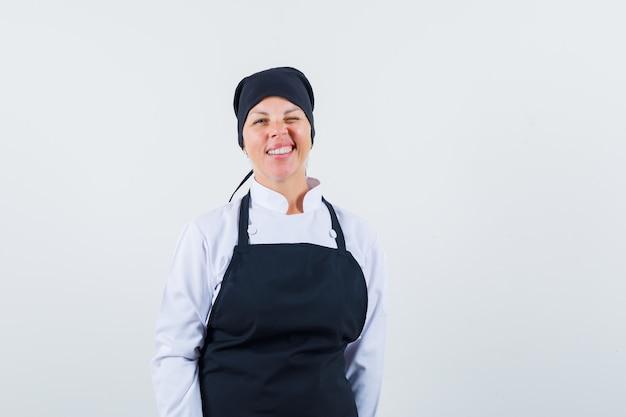 Mulher loira com uniforme de cozinheira preta em pé, posando na frente e bonita