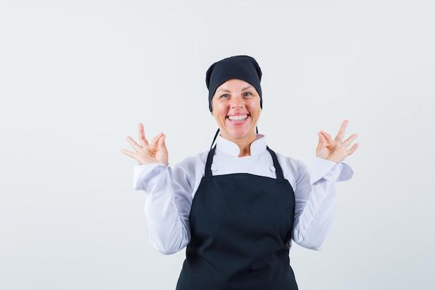 Mulher loira com uniforme de cozinheiro preto, mostrando sinais de ok com as duas mãos e olhando feliz, vista frontal.