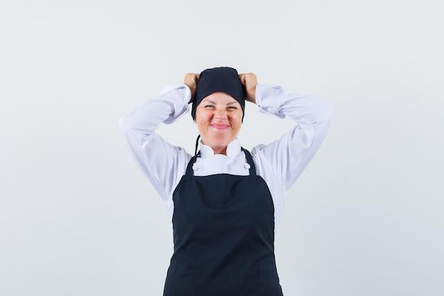 Mulher loira com uniforme preto de cozinheira de mãos dadas na cabeça, fazendo careta e linda