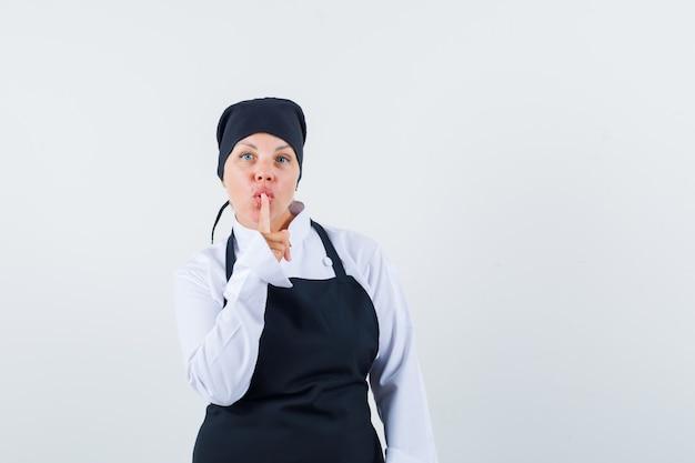 Mulher loira com uniforme preto de cozinheira mostrando gesto de silêncio e bonita