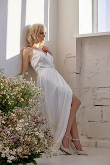 Mulher loira com vestido de noiva branco perto da janela em frente a um buquê de flores silvestres