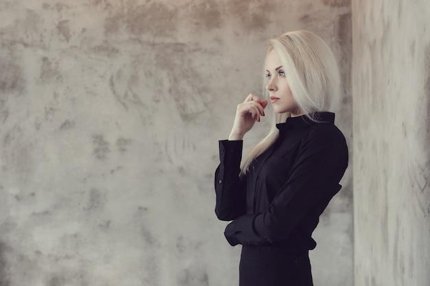 Mulher loira com vestido preto posando