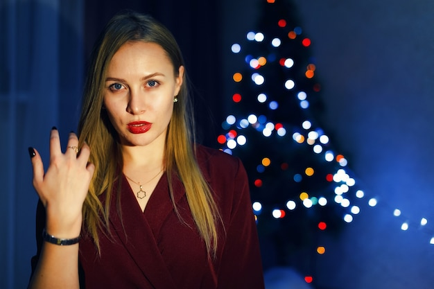Mulher loira com vestido vermelho contra a árvore de natal em casa. decorações de ano novo