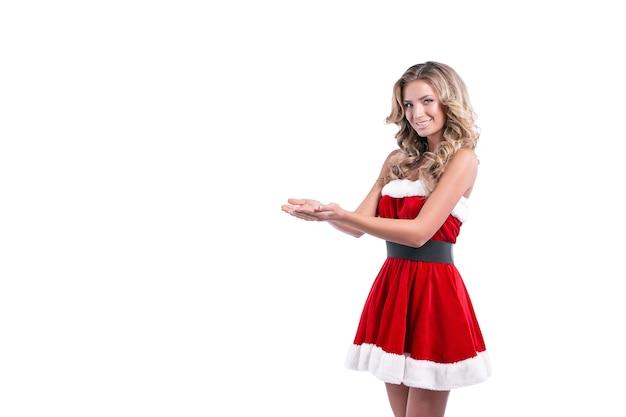 Mulher loira com vestido vermelho de papai noel posando sobre fundo branco.