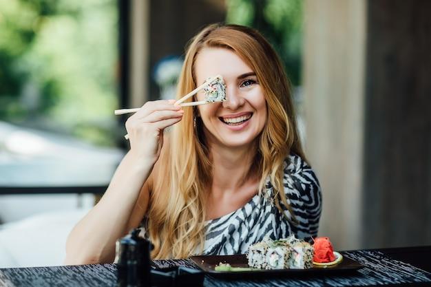 Mulher loira comendo sushi no restaurante