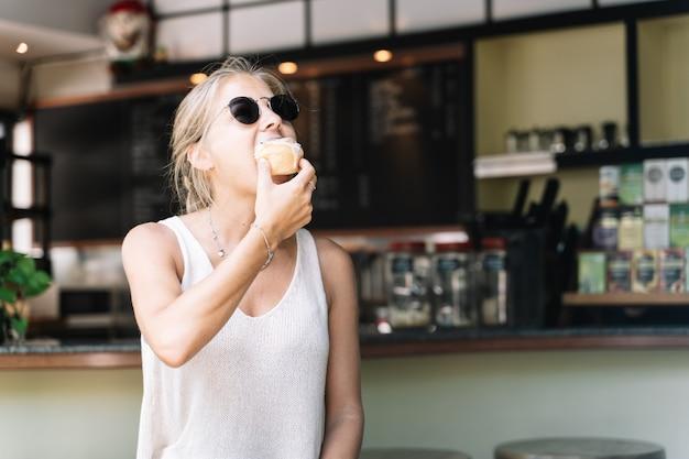 Mulher loira comendo um rolo de canela em um café