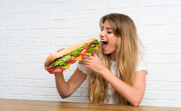 Mulher loira comendo um sanduíche gigante