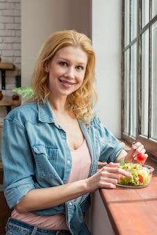 Mulher loira comendo uma salada