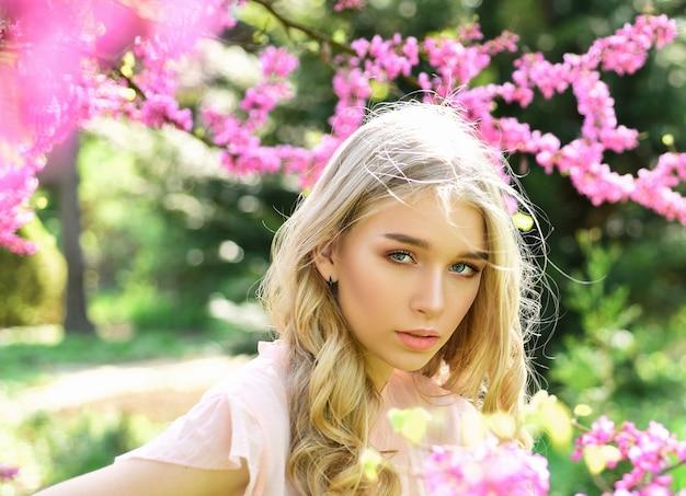 Mulher loira concurso perto de flores violetas da árvore de judas. flor da primavera. garota caminhando no parque primavera e apreciando flores no jardim