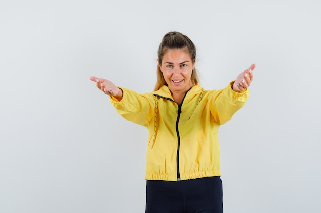 Mulher loira convidando para entrar com uma jaqueta bomber amarela e calça preta e parecendo feliz