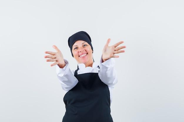 Mulher loira convidando para entrar em uniforme de cozinheira preta e bonita