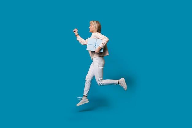 Mulher loira correndo está segurando uma caixa de presente na parede azul do estúdio e sorrindo em roupas casuais