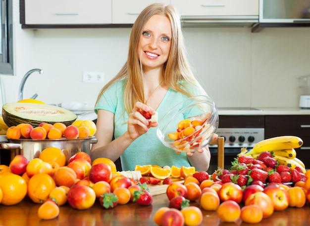 Mulher loira cozinhando salada de frutas