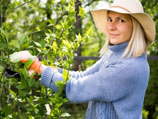 Mulher loira cuidando de suas plantas