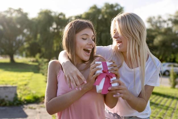 Mulher loira dando um presente para uma amiga