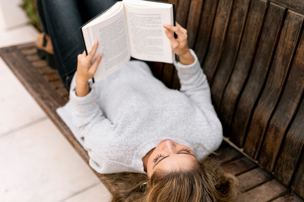 Mulher loira de alto ângulo lendo em um banco