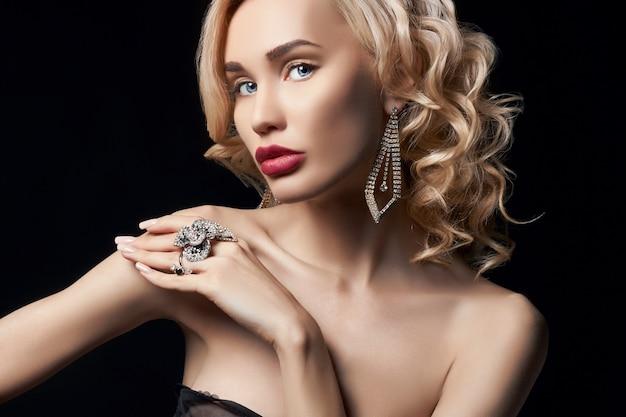 Mulher loira de beleza de moda. menina com joias nos braços e pescoço. cuidados com a pele e belas meninas perfeitas de maquiagem. mulher luxuosa com cabelo cacheado elegante