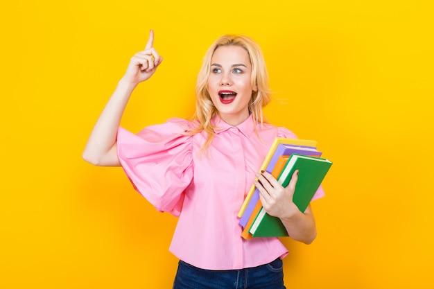 Mulher loira de blusa rosa com pilha de livros