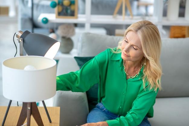 Mulher loira de blusa verde, olhando ocupado escolhendo móveis