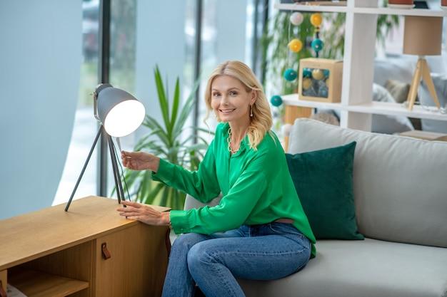 Mulher loira de blusa verde, sentado perto da lâmpada