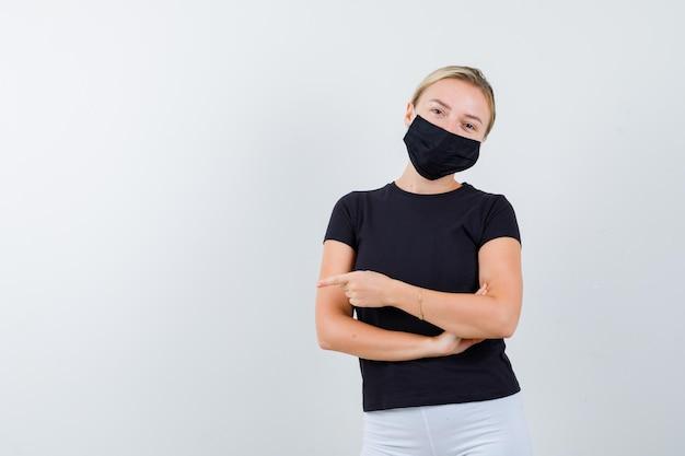 Mulher loira de braços cruzados, apontando para a esquerda com o dedo indicador em uma camiseta preta