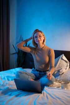 Mulher loira de cabelo curto na cama branca em jeans com um computador portátil.