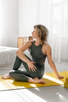 Mulher loira de cabelos cacheados fazendo ioga em casa