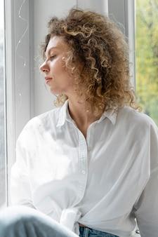 Mulher loira de cabelos cacheados relaxando em casa