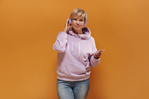 Mulher loira de cabelos curtos com capuz elegante rosa e jeans da moda, posando com fones de ouvido legais em fundo laranja isolado.
