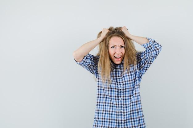 Mulher loira de camisa arrancando o cabelo e parecendo ansiosa,