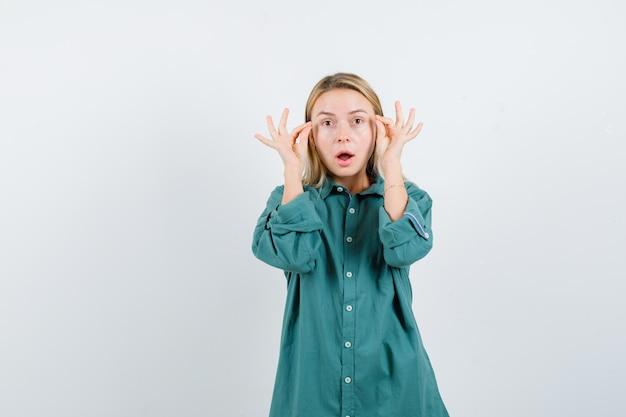 Mulher loira de camisa verde fingindo fazer maquiagem e parecendo maravilhada