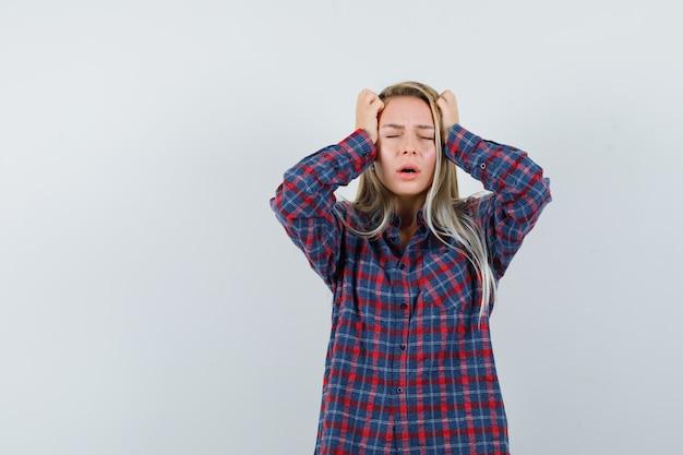 Mulher loira de camisa xadrez, colocando as mãos na cabeça, em pé com a boca aberta e parecendo aflita, vista frontal.