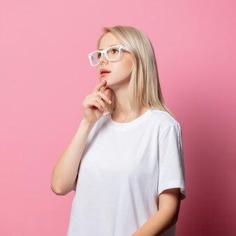 Mulher loira de camiseta branca e óculos