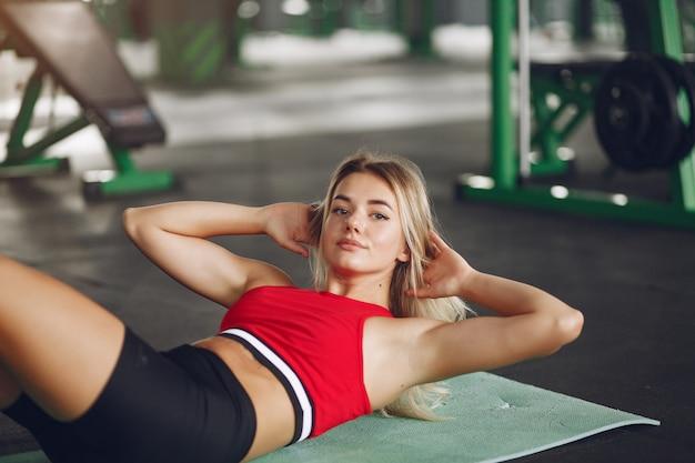 Mulher loira de esportes em um treinamento de sportswear em uma academia