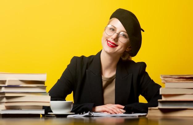 Mulher loira de estilo na boina, sentado à mesa com livros em amarelo