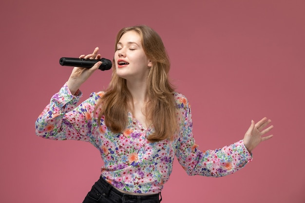 Mulher loira de frente cantando com seu microfone