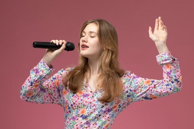 Mulher loira de frente cantando uma música com o coração