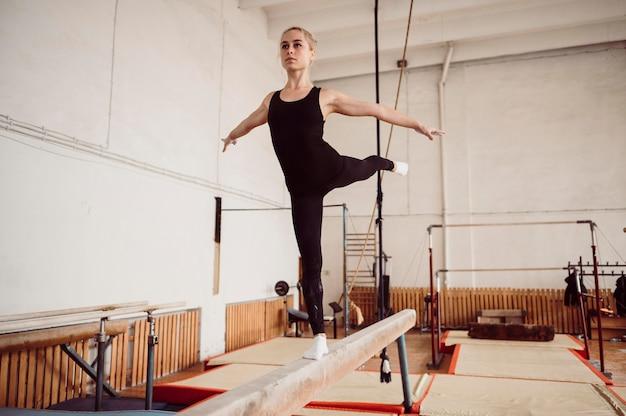 Mulher loira de frente para treinar na trave de equilíbrio