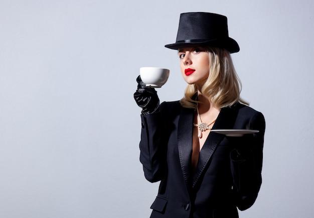 Mulher loira de jaqueta preta e cartola com uma xícara de café na parede branca
