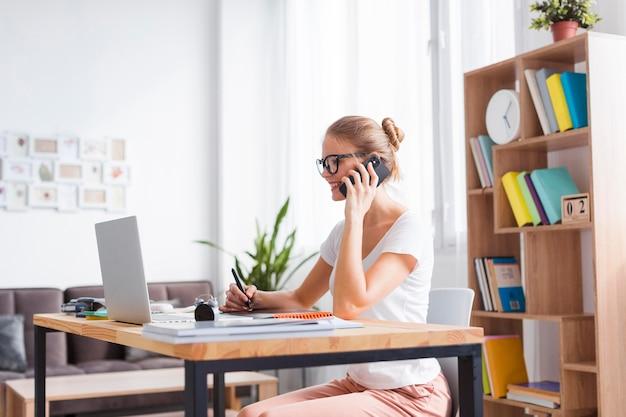 Mulher loira de lado falando ao telefone