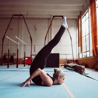 Mulher loira de lado treinando para as olimpíadas de ginástica