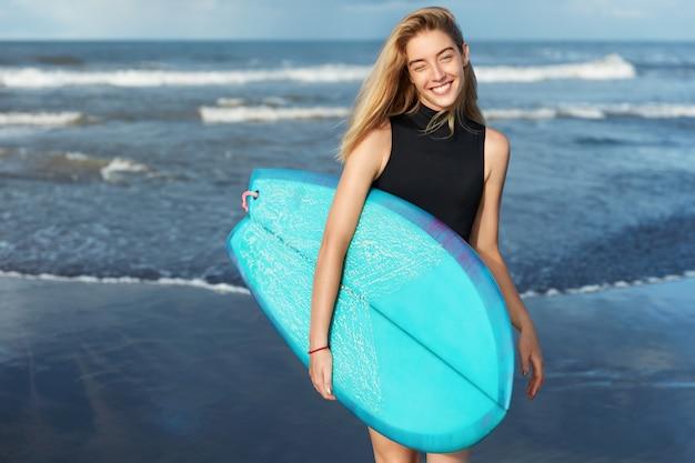 Mulher loira de maiô com prancha de surf na praia