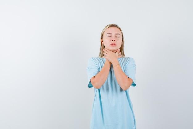 Mulher loira de mãos dadas no pescoço, com dor no pescoço, com camiseta azul